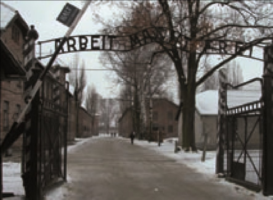 The gates of Auschwitz I and the original brick barrack buildings of the first site.jpg