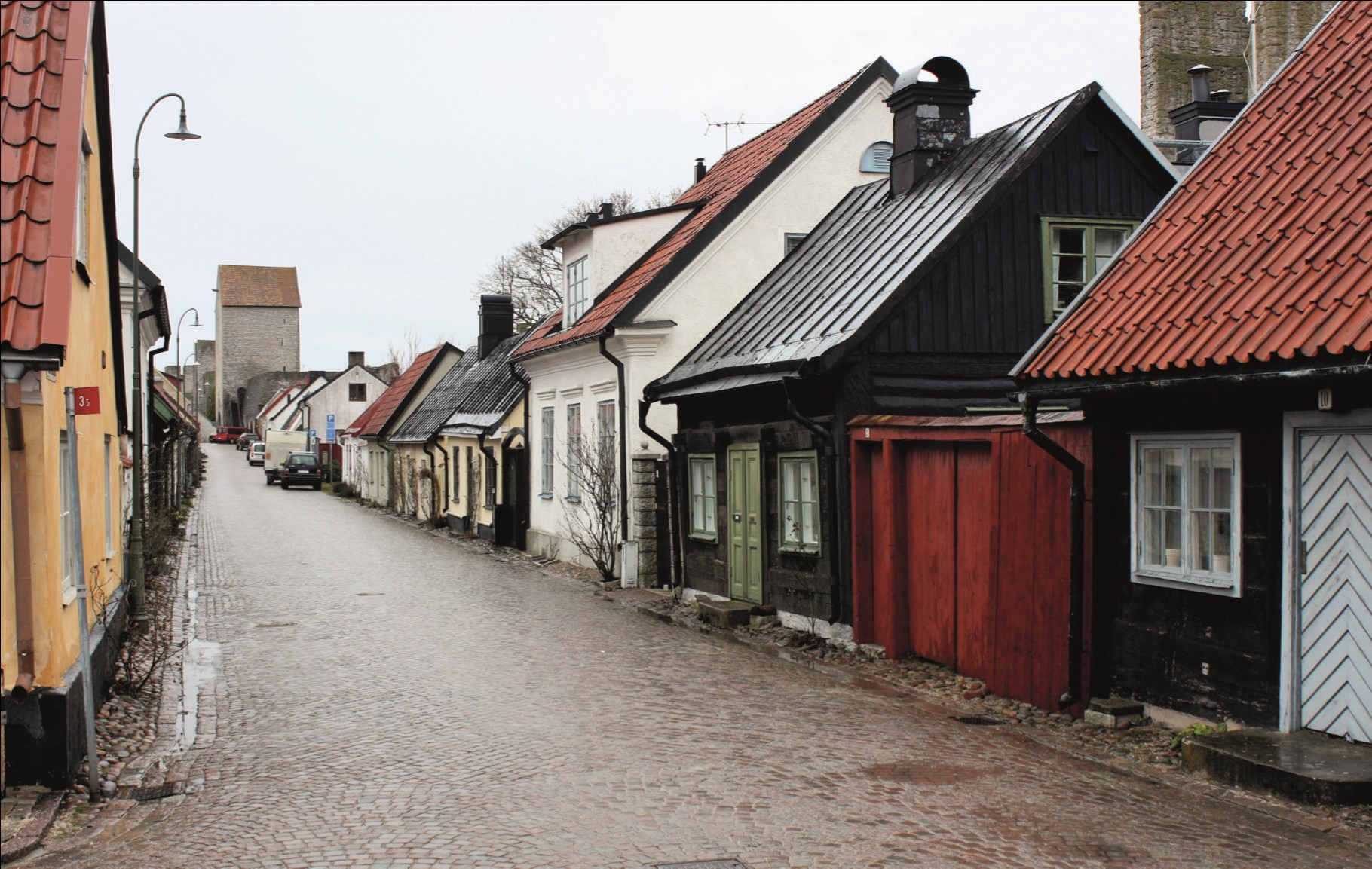 Wooden buildings next to the city walls at Visby.jpg